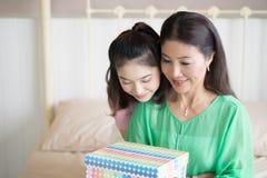 Hija adolescente que da el presente de cumpleaños a la madre que la abraza con Imagen de archivo libre de regalías