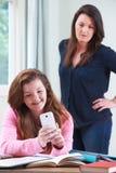 Hija adolescente que usa el teléfono móvil mientras que estudia Foto de archivo libre de regalías