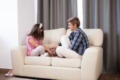Hija adolescente y su madre en el sofá Fotografía de archivo libre de regalías