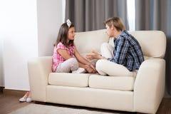 Hija adolescente y su madre en el sofá Fotos de archivo