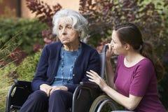 Hija adulta que conforta a la madre mayor en silla de ruedas Fotos de archivo