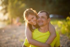 Hija adulta que disfruta a cuestas de paseo en sus padres detrás foto de archivo