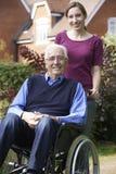 Hija adulta que empuja al padre In Wheelchair Foto de archivo libre de regalías