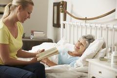 Hija adulta que lee al padre femenino mayor en cama en casa Imágenes de archivo libres de regalías
