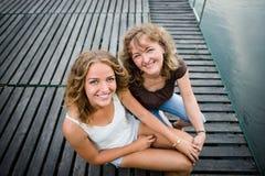 Hija alegre con la madre que se sienta en el embarcadero de madera Foto de archivo libre de regalías