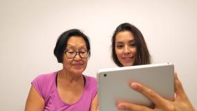 Hija asiática mayor de la mujer y de la raza mixta que hace las fotos divertidas del selfie con la tableta móvil 4K almacen de video