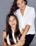 Hija bastante adolescente linda con la madre madura que abraza, maquillaje de la morenita del estilo de la moda Fotos de archivo libres de regalías