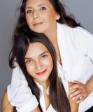 Hija bastante adolescente linda con la madre madura que abraza, maquillaje de la morenita del estilo de la moda Fotos de archivo