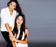 Hija bastante adolescente linda con la madre madura que abraza, morenita del estilo de la moda Foto de archivo libre de regalías