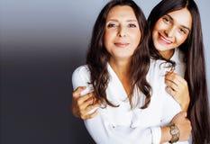 Hija bastante adolescente linda con la madre madura que abraza, morenita del estilo de la moda Imágenes de archivo libres de regalías