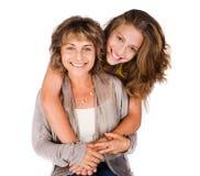 Hija bonita que abraza a su mama de la parte posterior Foto de archivo