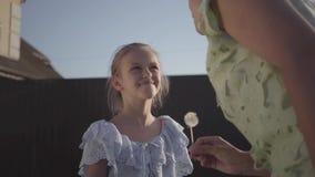 Hija buena agradable que da a su madre una flor del diente de león y que sonríe en ella por la tarde del verano en el pueblo almacen de metraje de vídeo