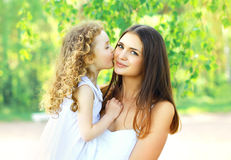 Hija cariñosa que besa la madre, la mamá joven feliz y al niño en día de verano soleado caliente en la naturaleza Foto de archivo libre de regalías