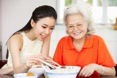Hija china de la madre y del adulto que come la comida Imagen de archivo libre de regalías