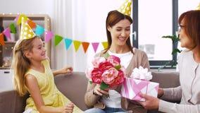 Hija con la madre del saludo de la caja de regalo en cumpleaños metrajes