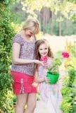 Hija con la madre en el jardín del verano Imagen de archivo libre de regalías