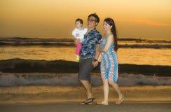 Hija coreana asiática feliz y hermosa joven del bebé de la tenencia de la pareja que camina en la playa de la puesta del sol que  fotos de archivo libres de regalías
