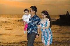 Hija coreana asiática feliz y hermosa joven del bebé de la tenencia de la pareja que camina en la playa de la puesta del sol que  imágenes de archivo libres de regalías