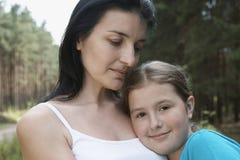 Hija de abarcamiento de la madre al aire libre Foto de archivo