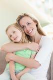 Hija de abarcamiento de la madre en el sofá Fotos de archivo libres de regalías
