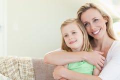 Hija de abarcamiento de la madre en el sofá Foto de archivo