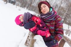 Hija de abarcamiento de la madre en invierno Fotos de archivo libres de regalías