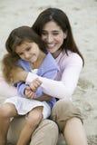 Hija de abarcamiento de la madre en la playa Imagen de archivo libre de regalías