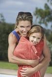 Hija de abarcamiento de la madre envuelta en toalla Fotografía de archivo
