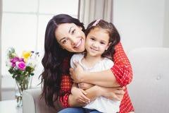 Hija de abarcamiento de la madre feliz en casa Imagen de archivo libre de regalías