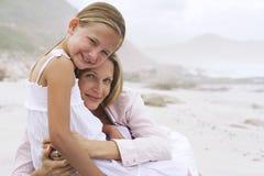 Hija de abarcamiento de la mujer en la playa Imagen de archivo libre de regalías
