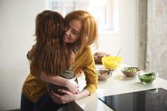 Hija de abarcamiento de la madre que cuida en cocina Fotos de archivo libres de regalías