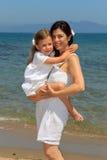 Hija de abrazo de la madre en una playa Imagenes de archivo