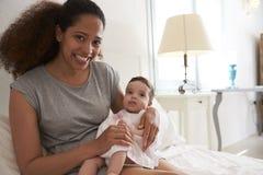 Hija de abrazo del bebé de la madre en dormitorio en casa Fotos de archivo