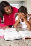 Hija de ayuda de la madre con la preparación Foto de archivo libre de regalías