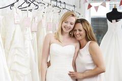 Hija de ayuda de la madre para elegir el vestido en tienda nupcial Imagen de archivo