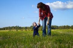 Hija de ayuda de la madre que hace los primeros pasos Fotografía de archivo libre de regalías