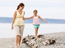 Hija de ayuda de la madre recorrer en registro en la playa Fotografía de archivo libre de regalías