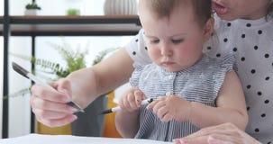 Hija de ayuda del bebé de la madre a dibujar en el papel almacen de video