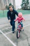 Hija de ayuda de la muchacha del entrenamiento del padre para montar la bicicleta foto de archivo