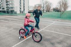 Hija de ayuda de la muchacha del entrenamiento del padre para montar la bicicleta foto de archivo libre de regalías