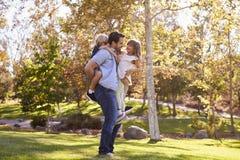 Hija de Carrying Son And del padre como juegan en parque foto de archivo libre de regalías