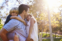 Hija de Carrying Son And del padre como juegan en parque fotos de archivo