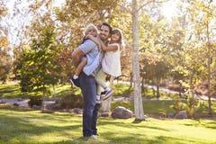 Hija de Carrying Son And del padre como juegan en parque fotografía de archivo libre de regalías
