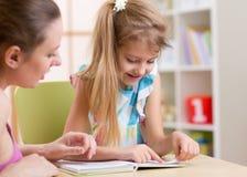 Hija de enseñanza del niño de la madre a leer fotografía de archivo libre de regalías