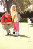 Hija de enseñanza del padre para jugar a golf Fotos de archivo libres de regalías