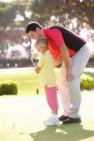 Hija de enseñanza del padre para jugar a golf Imágenes de archivo libres de regalías