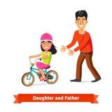 Hija de enseñanza del padre para montar una bicicleta Imagen de archivo