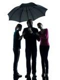 Hija de la madre del padre de la familia bajo el paraguas   Foto de archivo libre de regalías