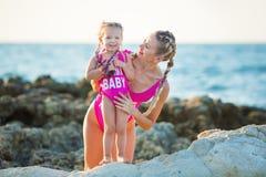 Hija de la madre que se divierte que descansa sobre la playa rocosa que lleva los trajes que nadan rosados La señora rubia con la imágenes de archivo libres de regalías