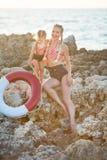 Hija de la madre que se divierte que descansa sobre la playa rocosa La señora rubia dos que lleva los trajes que nadan retros dis fotografía de archivo